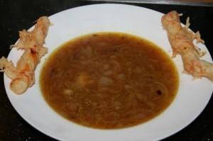 Zwiebelsuppe mit eleganten Käsestangen serviert